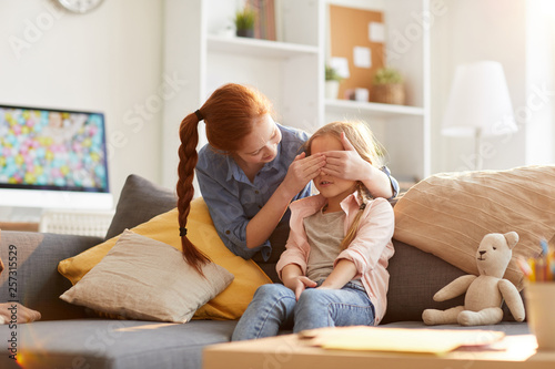 Fotografie, Obraz  Portrait of two sisters playing hide and seek at home, focus on little girl coun