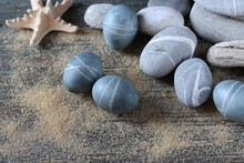 Easter  In A Nautical Style. Easter Eggs Painted Tea Hibiscus Gray, Tied With A Rope, Get Light Streaks. And The Result Is An Egg Like Pebbles Stones. Eggs Still As Stones And Natural Stones.