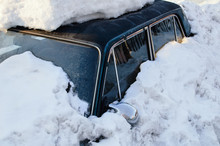 Dark Blue Car Covered With Snow Drift. In The Winter Outside.