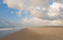 A Deserted Sandy Beach With White Clouds And Blue Sky