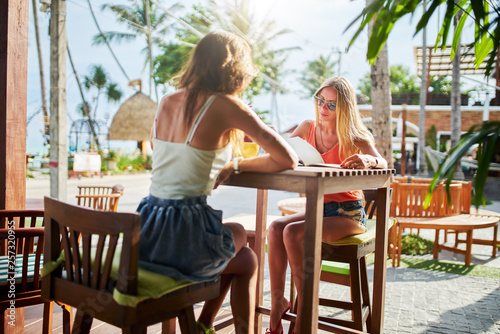 Cuadros en Lienzo two female tourists looking at menu at beachside cafe in koh samui thailand
