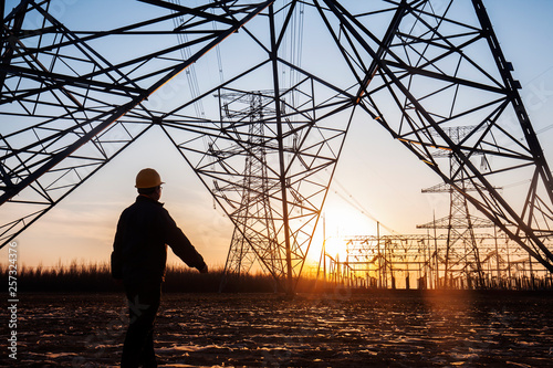 Fotografia electricity workers and pylon silhouette