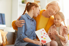 Waist Up Portrait Of Mature Woman Embracing Two Beautiful Girls At Home, Scene Lit By Warm Sunlight, Copy Space