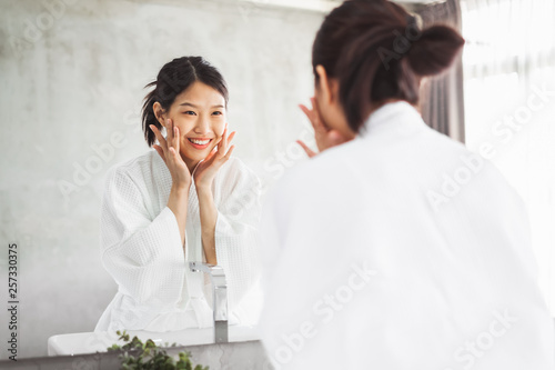 Fotografiet  Asian woman cleaning face front of mirror, skin care and cosmetic removal concep