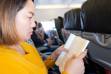 Asian Woman Reading Book On Plane