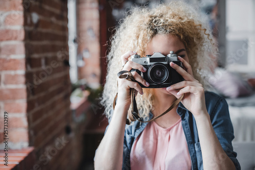 Photo  Curly blonde woman holding her retro photo camera at home.