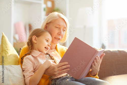 Portrait of smiling mature woman reading book to cute little girl in sunlight, c Canvas Print