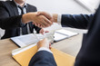 Dealing greeting and partnership meeting concept, businessmen handshaking after finishing up deal contract for both companies.