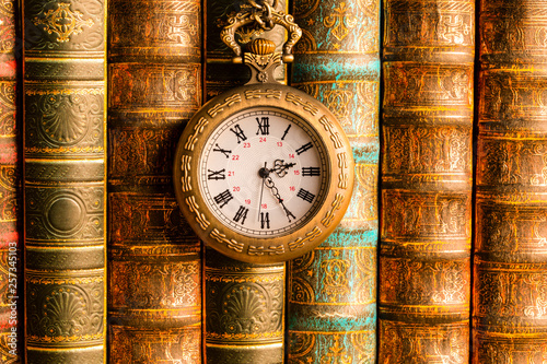 Foto  Antique clock on the background of vintage books