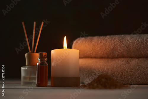 Towels, candle and massage oil on white table
