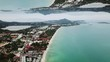 Aerial view of the coastal small town and the turquoise sea with a horizon mirror effect. Beautiful sea shore with a city and mountains, inception theme.