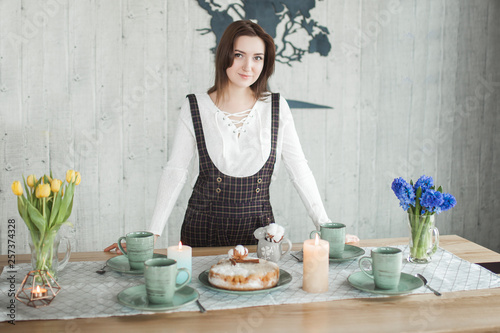 Poster Cuisine Young housewife at the dinner table. Woman with charlotte pie. Female on the loft kitchen. Lady drinking tea with apple cake.