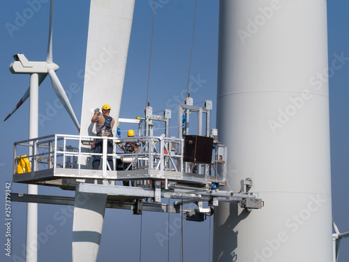 Workers on a hanging platform repair a damaged rotor blade on a wind turbine Canvas Print