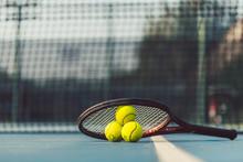 Three Tennis Balls On A Professional Racket On Acrylic Blue Surface