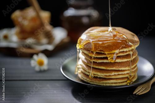 Honey dripping on the stack of pancakes for breakfast on the wooden table, healt Fototapeta