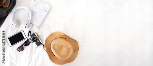 Fototapeta Summer travel items on blanket on bed.Top view of accessories travel (camera,hat,headphone,map ) on bed blankket.prepareing for holiday vacation trip.journey planning.banner for display of design. obraz