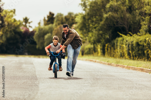 Fotografía  Father teaching his son to ride a bicycle
