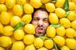 canvas print picture - Mann mit Zitronen, Konzept für die Lebensmittelindustrie. Gesicht des lachenden Mannes in der Zitronenoberfläche.