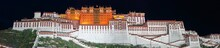 Panorama Of Potala Palace At Night (Lhasa, Tibet, China). Black Sky, The Whole Palace Is Illuminated And Shines In Red And White. On Top Of The Home Of The Dalai Lama Waves The Chinese Flag.