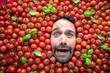Mann mit Tomaten, Konzept für die Lebensmittelindustrie. Gesicht des lachenden Mannes in der Tomatenfläche.