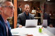 Businessman Working At Desk On Laptop In Open Plan Office With Colleagues In Background