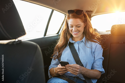 Casual woman using smartphone in car Billede på lærred