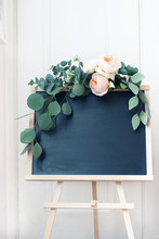 Empty Wedding Chalkboard Sign Mockup Scene. Floral Garland Of Eucalyptus Branches And Apricot English Roses Flowers. Rustic Birthday Party Decoration. Wooden Easel With Welcome Board. Vertical.