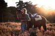 canvas print picture - Frau umarmt Pferd in der Heide