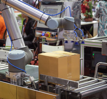 The Universal Robot Lifting Cardboard To Conveyor In Industry Production Line