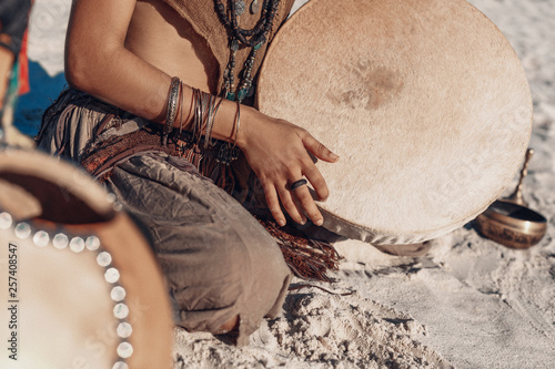 Canvastavla shaman drum in woman hand. playing ethnic music