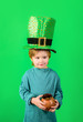 canvas print picture - Kid dressed in green with St. Patrick's hat. Child with hat of Saint Patrick's Day celebration. Cute guy in big hat of Saint Patrick Day. Little boy in Leprechaun hat holds pot of gold. Irish holiday.