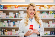 Smiling Pharmacist Holding Medication, Looking At Camera.