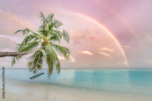 Wall Murals Light pink Perfect tropical landscape, sunset beach with palm tree and swing hanging under colorful rainbow. Romantic beach landscape