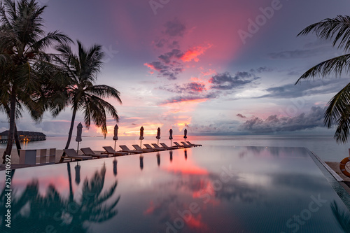 Fototapety, obrazy: Beautiful poolside and sunset sky. Luxurious tropical beach landscape, deck chairs and loungers and water reflection