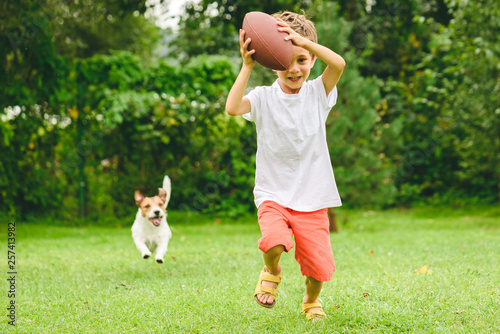 Photo  Kid playing american football ready to make touchdown and dog chasing him