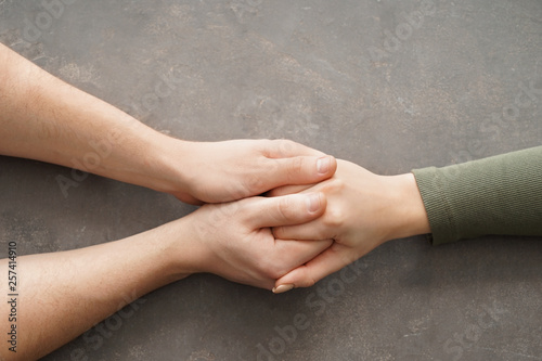 Carta da parati  Hands of man comforting young woman on grey background