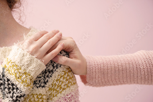 Photo Young woman comforting her friend on color background