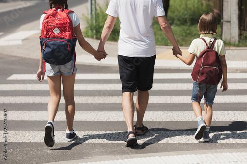 Responsible parent holding hands of children while walking through crosswalk Fotobehang