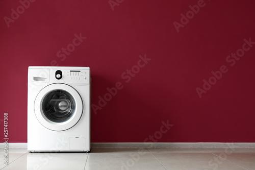 Fototapeta  Modern washing machine near color wall