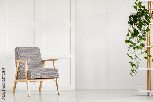 Fotografie, Obraz  Vintage armchair next to an empty wall in a daily room interior