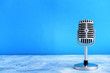 canvas print picture - Retro microphone on table against color background