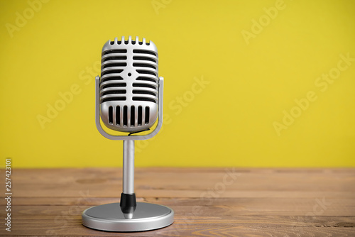 Photo  Retro microphone on table against color background