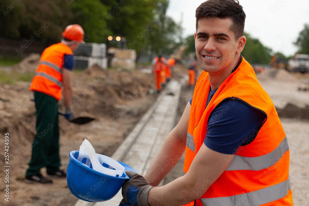 Fototapeta Handsome young road construction worker in orange safety jacket