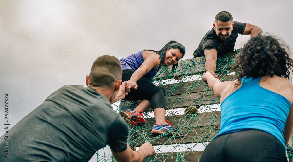 Fototapety, obrazy: Group of participants in an obstacle course climbing a net