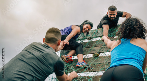 Valokuva Group of participants in an obstacle course climbing a net