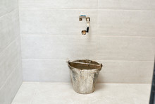 DIY, Ceramic Brick Tile Wall In A Bathroom Improvements Room Construction. Tap And Filled Bucket Water.