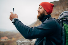 Side View Portrait Of Young Man Taking Photo In Mountains From His Smart Phone. Traveler Bearded Male Wearing Red Hat Take Selfie From Mobile Phone After Hiking. Travel, Lifestyle