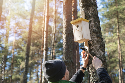 Photo man nailing birdhouse on the tree trunk in the forest