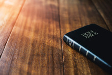 Holy Bible On Wooden Table Background With Soft Morning Sun Light