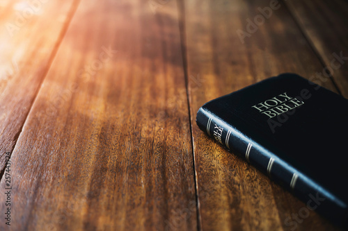 Fotografia  holy bible on wooden table background with soft morning sun light